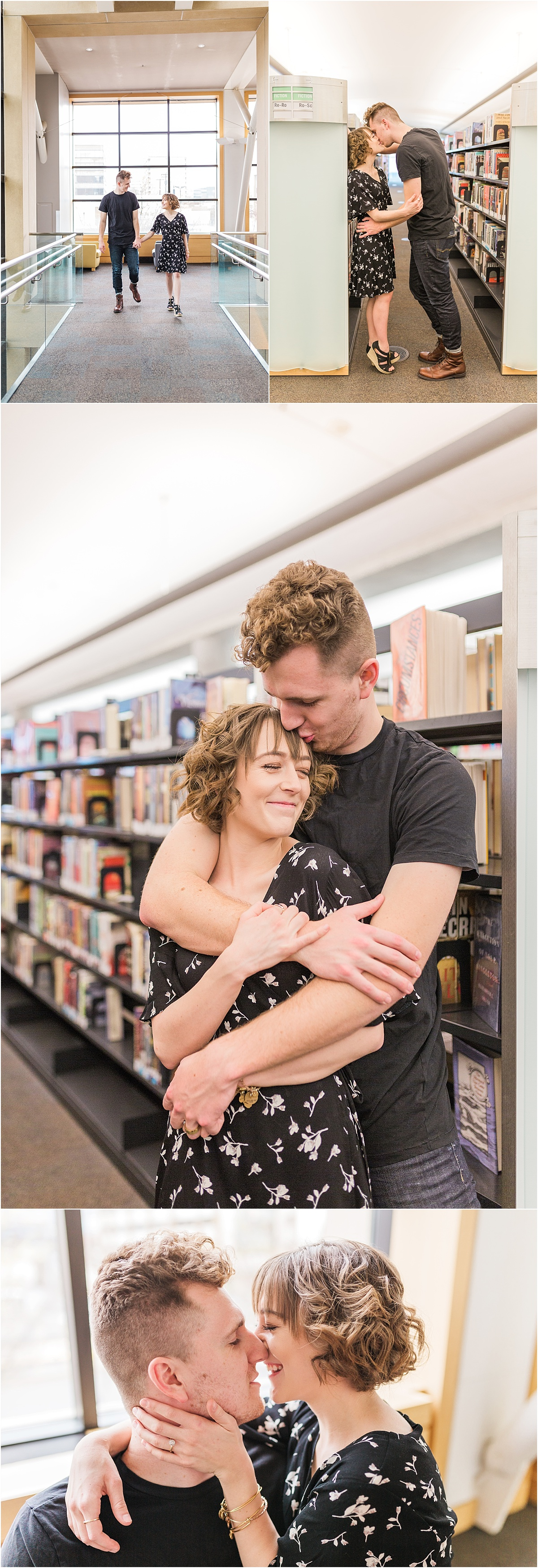A couple is inside of a modern looking library. The couple is hugging, kissing, and smiling amonst the bookshelves.